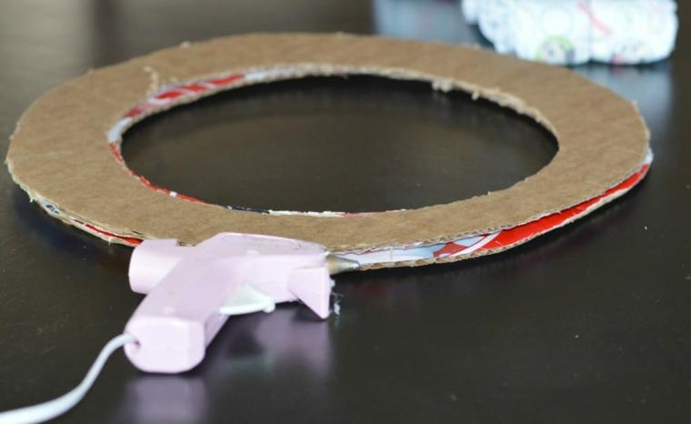 Come realizzare fiocchi nascita da esterno, cerchio di cartone accanto ad una pistola per colla a caldo