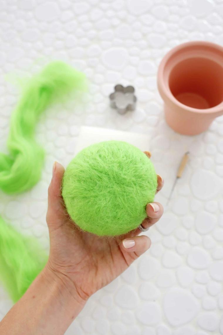 Rotolo di lana verde infeltrita, regalo festa dei nonni, rotolo di lana in mano di una donna
