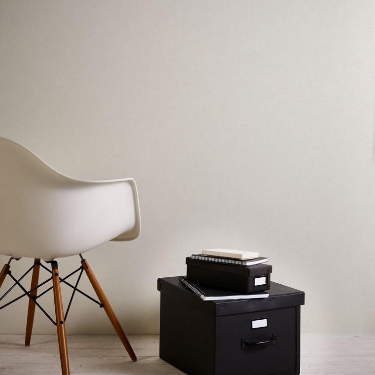 Scatole di cartone accanto ad una sedia, parete con carta da parati bianca