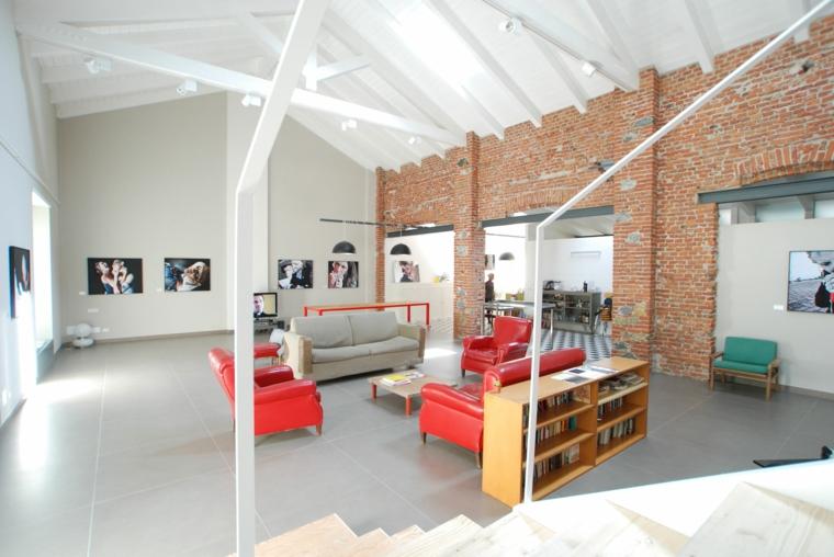 Soggiorno con pareti di mattoni a vista, divano e poltrone con tavolino basso