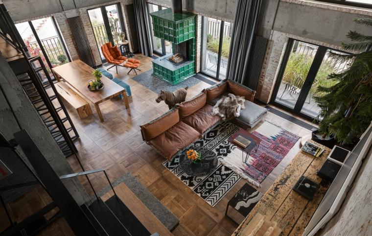 Open space con soppalco, soggiorno con divano in pelle e tavolino basso, tavolo da pranzo in legno con panchine