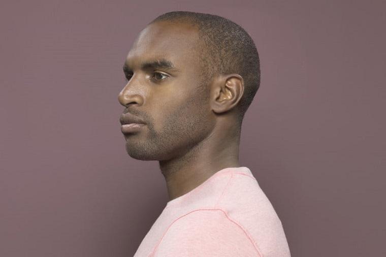 Come tagliarsi i capelli da solo, uomo con capelli rasati, viso di profilo su sfondo viola