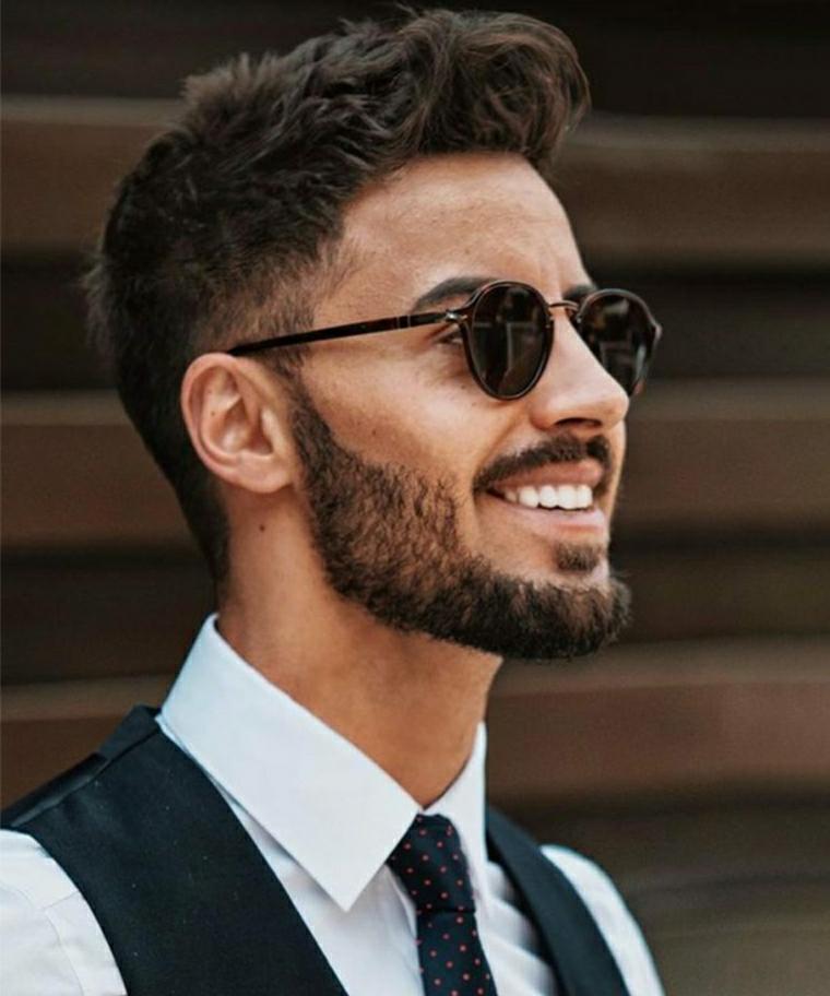 Uomo con viso sorridente e barba, capelli neri con ciuffi lunghi sopra