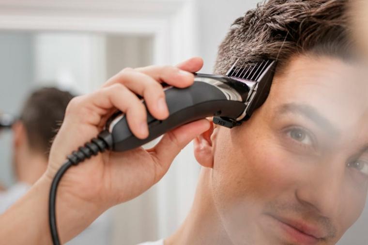 Ragazzo che si taglia i capelli con la macchinetta, come tagliarsi i capelli da solo