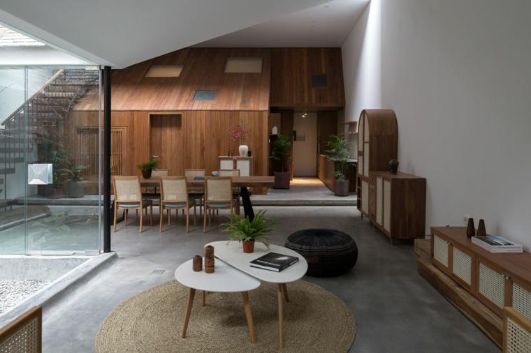 Parete con pannelli di legno, soggiorno con tavolini bassi, tavolo da pranzo con sedie