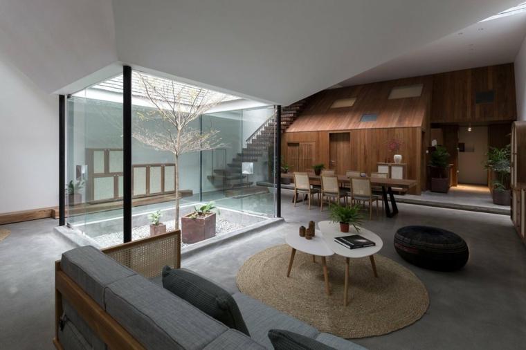Appartamento con giardino interno, soggiorno con divano e tavolini bassi