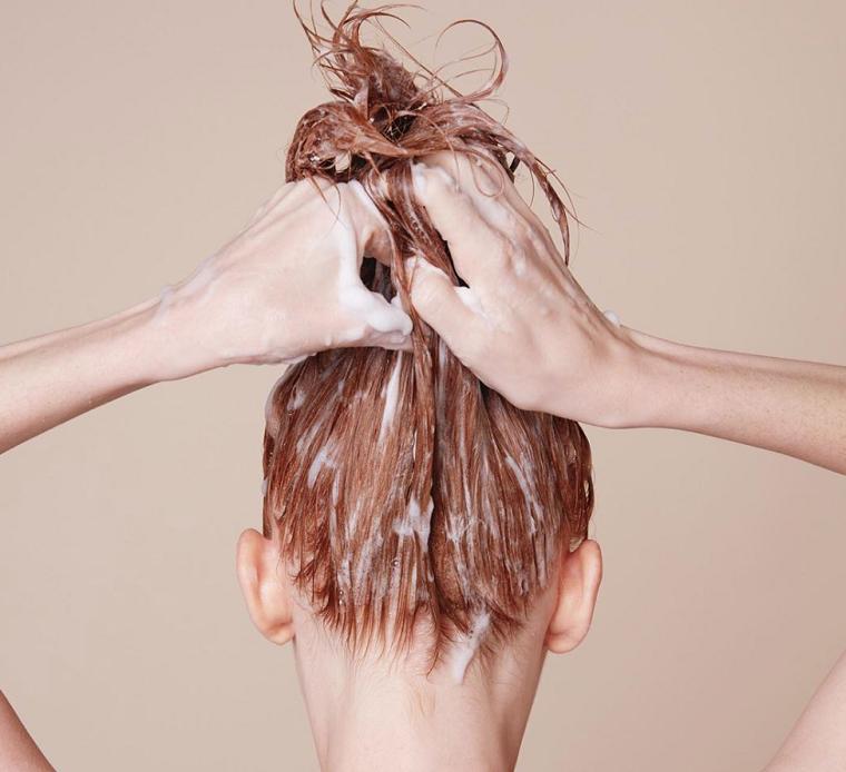 Ragazza con capelli biondi che si fa lo shampoo, maschera per capelli fatta a casa