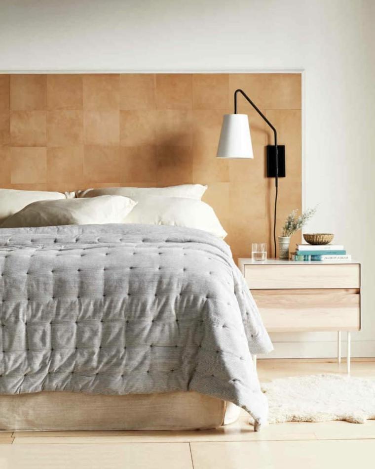 Pannello di legno come testata del letto, letto con coperta grigia, comodino con libri sopra