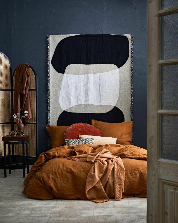 Camera da letto con parete blu, testata del letto con pannello in tessuto