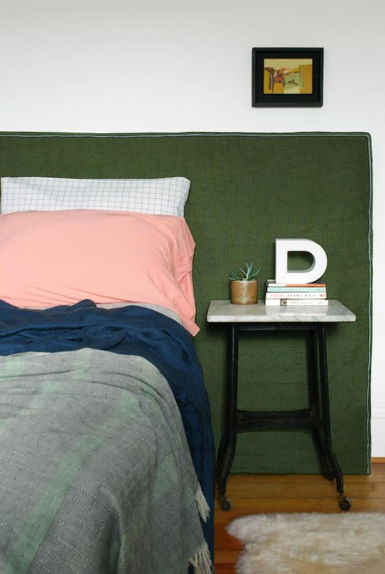 Comodino con libri e lettera decorativa, testa del letto in tessuto verde, come fare testiera del letto