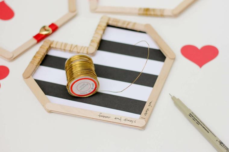 Fai da te con bastoncini di legno, cornice di legno con fili colorati e cuori di carta