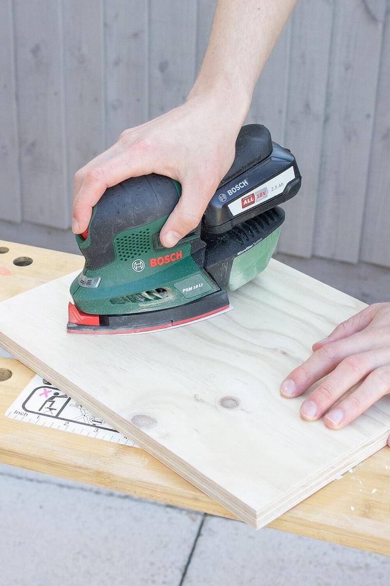 Oggetti in legno fai da te, uomo che lavora con la smerigliatrice su un pannello di legno