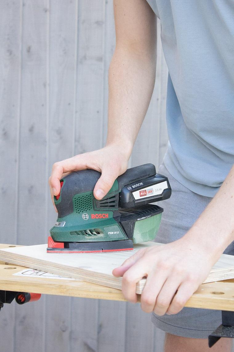 Invenzioni con il legno, uomo che lavora un pannello di legno con la smerigliatrice