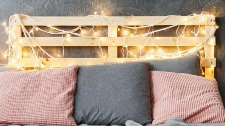 Testata del letto in pallet con fili di luci, letto con cuscini colorati