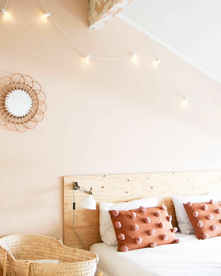Pannello di legno come testata del letto, cuscini colorati con pompon, fili di lucine