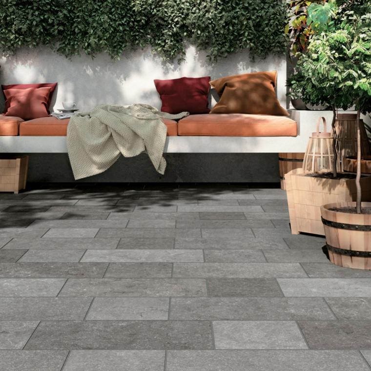 piastrelle in ceramica balcone colore grigio divano cuscini alberelli piante verdi