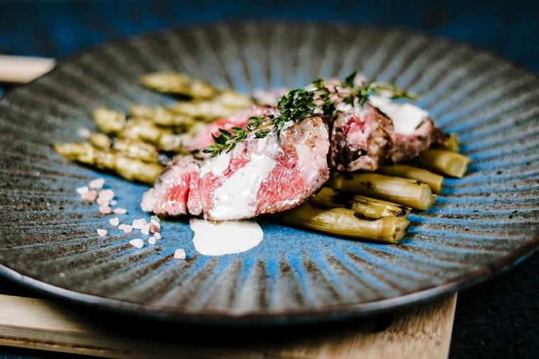 secondo piatto con base di asparagi e steak di manzo con panna