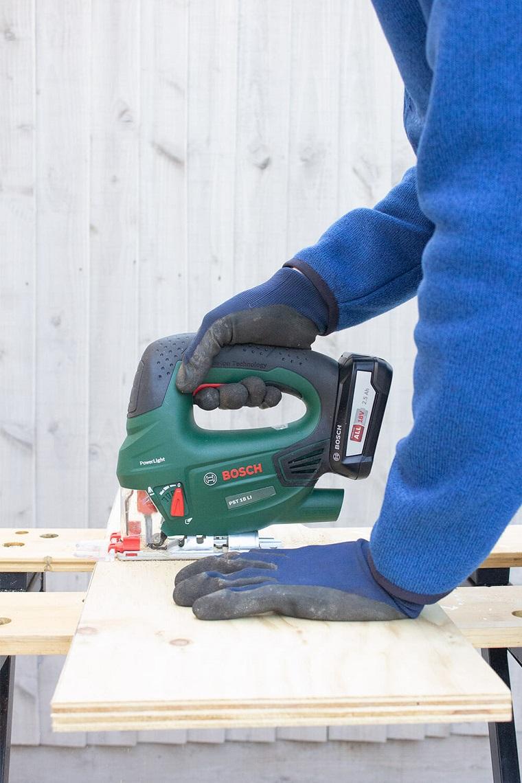 Uomo che taglia con seghetto elettrico un pezzo di legno, cosa costruire con il legno