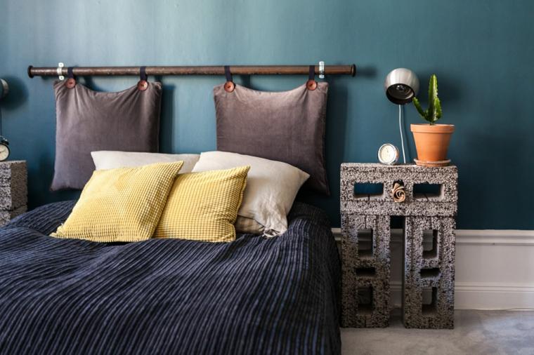 Camera da letto con testata in cuscini, comodino con mattoni, vaso con pianta grassa