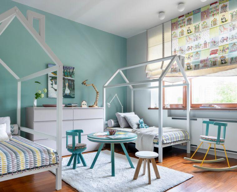 camerette due letti a terra mobile pareti verdi tavolino sedie finestra tende