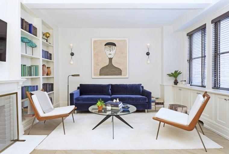 come posizionare i mobili in salotto divano tavolino rotondo due poltrone mensole libri quadri cornici