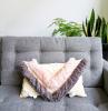 divano grigio cuscini nappe frange soggiorno vasi piante foglia verde