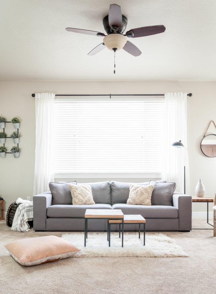 divano grigio tessuto tavolini bassi cuscino tappeto finestra tende lampadario