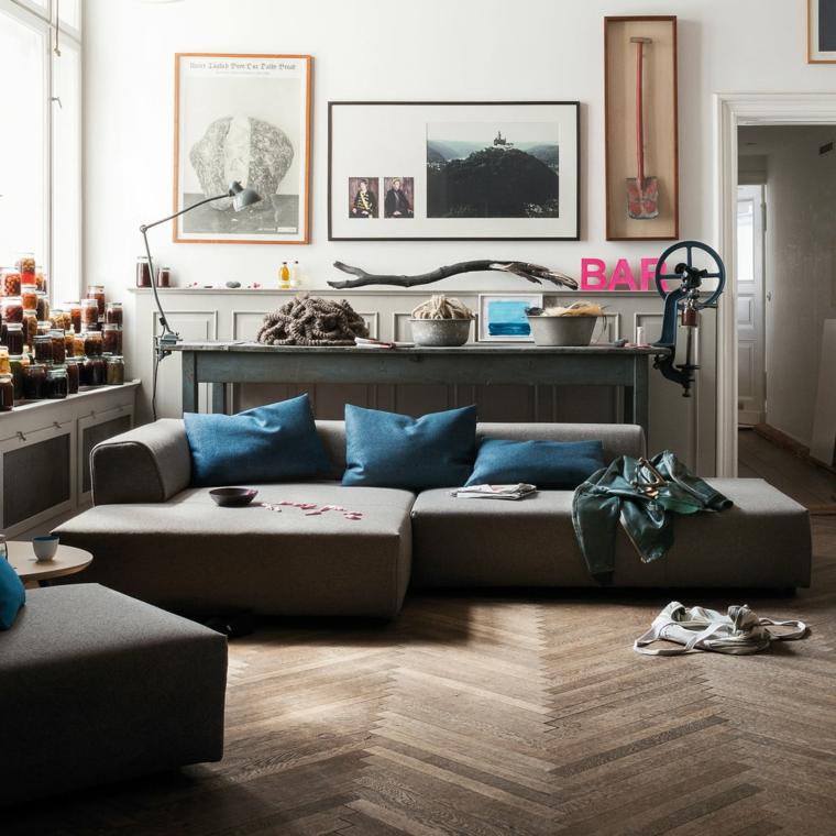 pavimento legno parquet divano cuscini decorazione parete quadri finestra