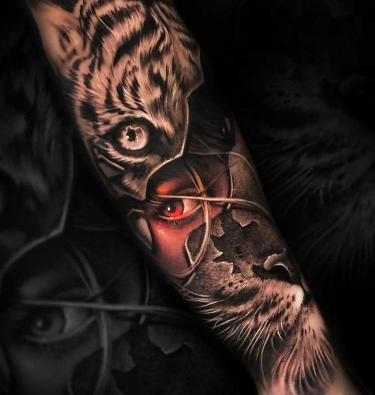 avambraccio di un uomo con disegni tatuaggi colorati di una donna e gatto