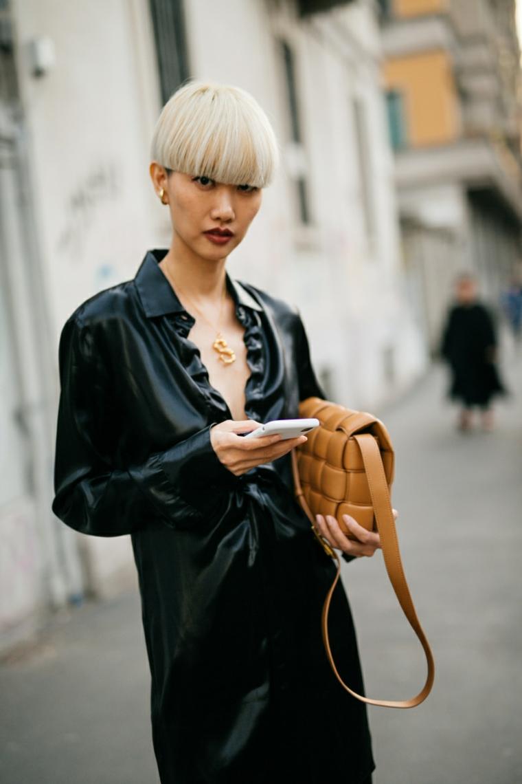 capelli corti biondi sfumati taglio caschetto frangia ragazza abito nero lungo borsa telefono