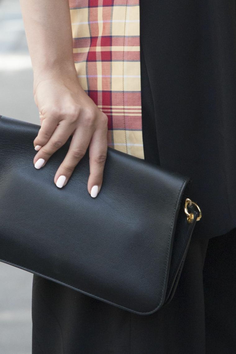 colori unghie 2020 smalto bianco donna con borsetta in mano manicure ovale corta