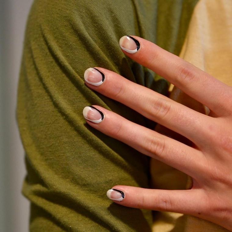 colori unghie autunno meta bianco nero manicure corta bicolore sulla mano di una donna