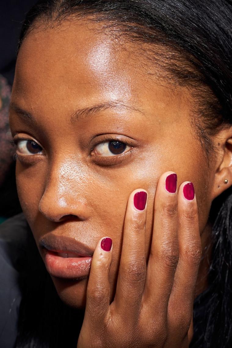colori unghie autunno smalto colore bordeaux manicure corta sulla mano di una ragazza