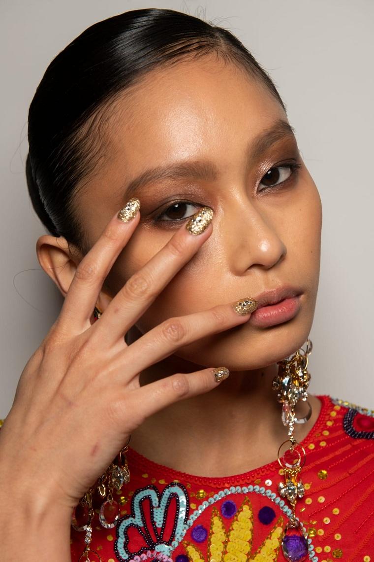 donna con capelli neri raccolti unghie a mandorla con smalto effetto sugar colore manicure oro glitter