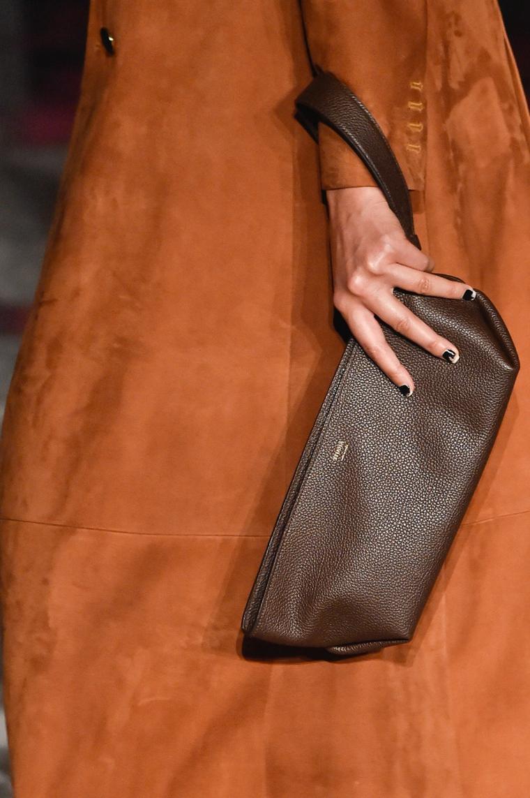 donna con cappotto e borsetta smalto semipermanente e colori manicure nero