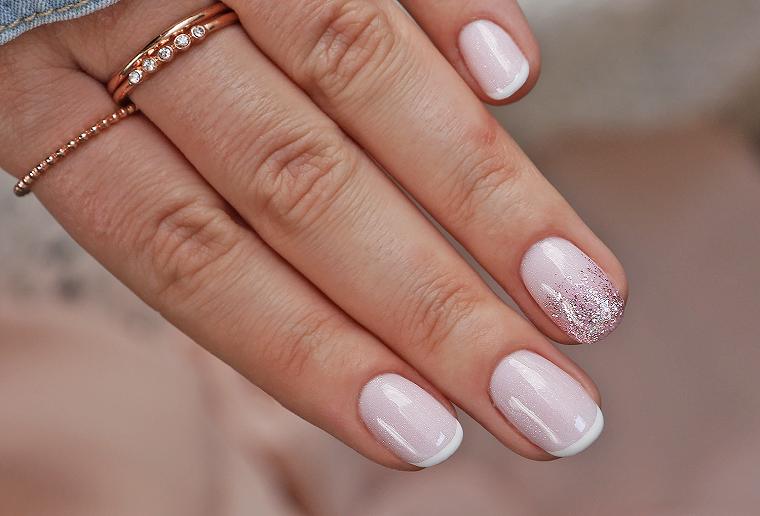 manicure con smalto rosa lucido accent nail argento anelli sulla mano di una donna