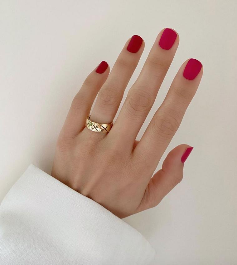 mano donna con smalto di colore rosso anello in oro unghie forma quadrata corte