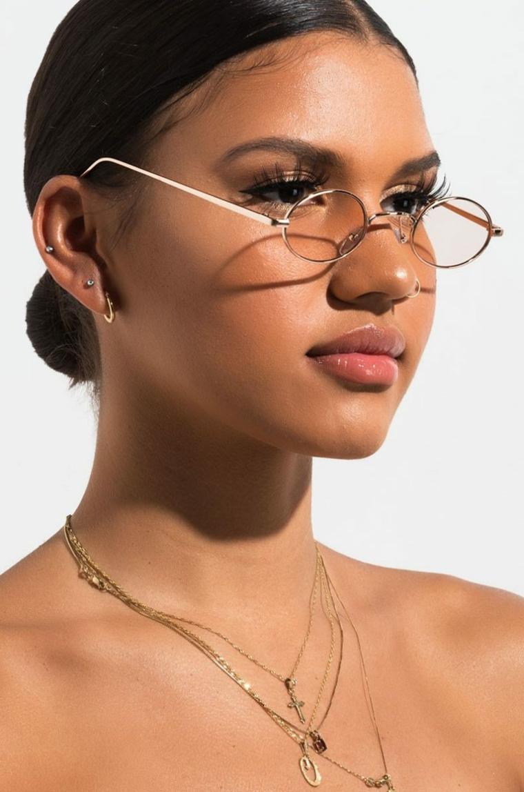 occhiali da vista a goccia indossati lenti colorate montatura metallo donna capelli raccolti collane