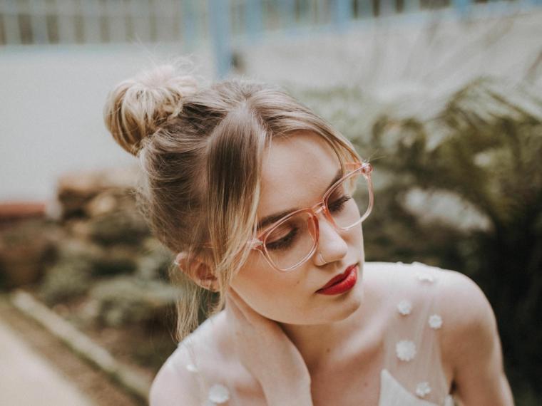 occhiali da vista a goccia indossati ragazza capelli biondi legati chignon rossetto