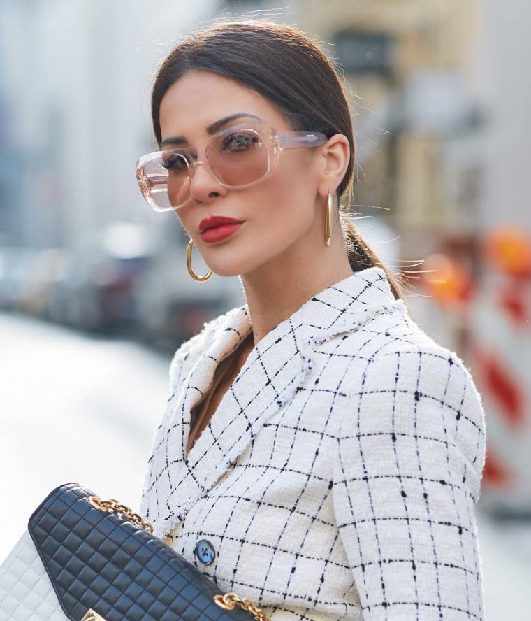 occhiali da vista trasparenti montatura acetato lenti colorate donna capelli raccolti castani giacca borsetta