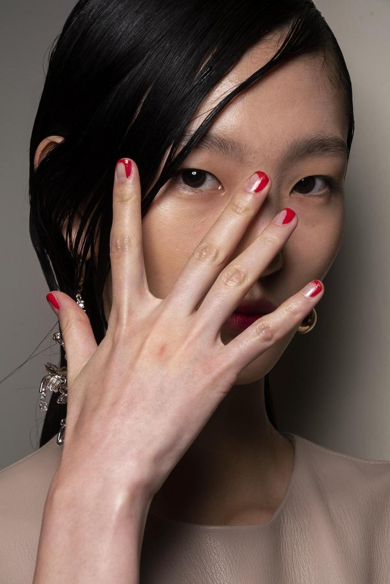 ragazza con unghie corte dipinte a meta manicure di colore rosso capelli raccolti