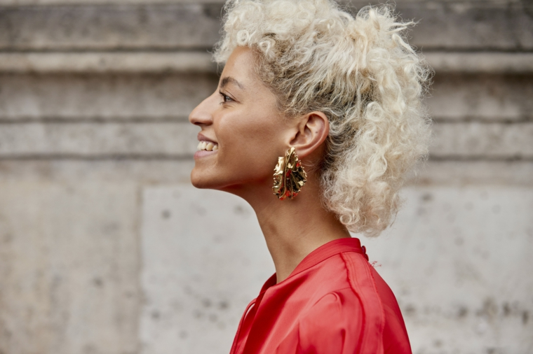 tagli e colori capelli 2020 biondo acconciatura ricci donna orecchini camicia rossa
