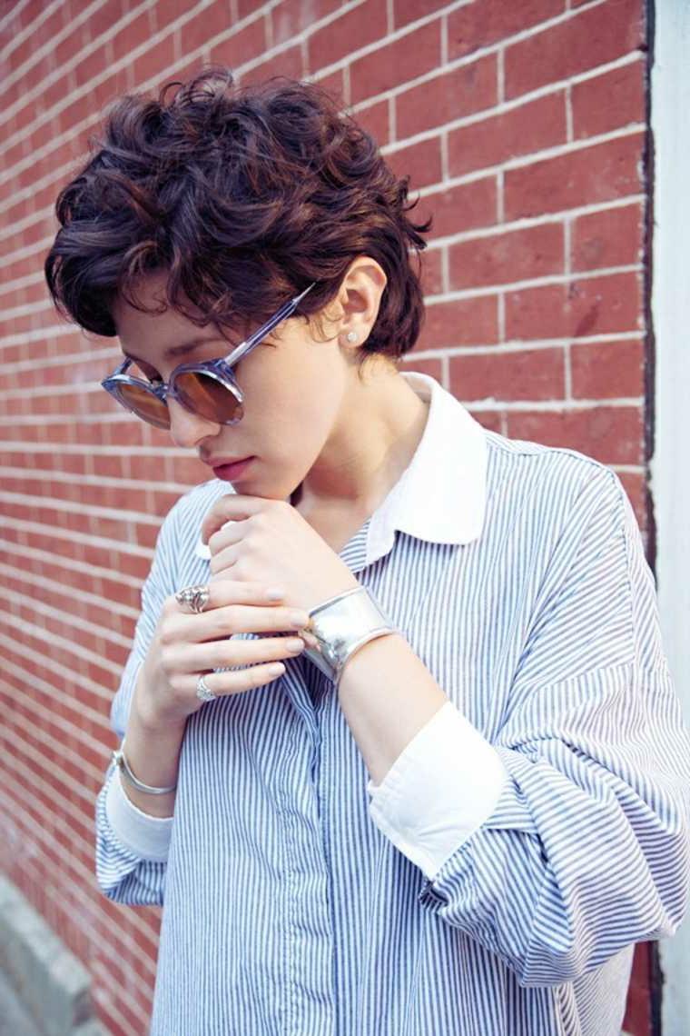 taglio corto ricci colore castano donna acconciatura occhiali da sole camicia