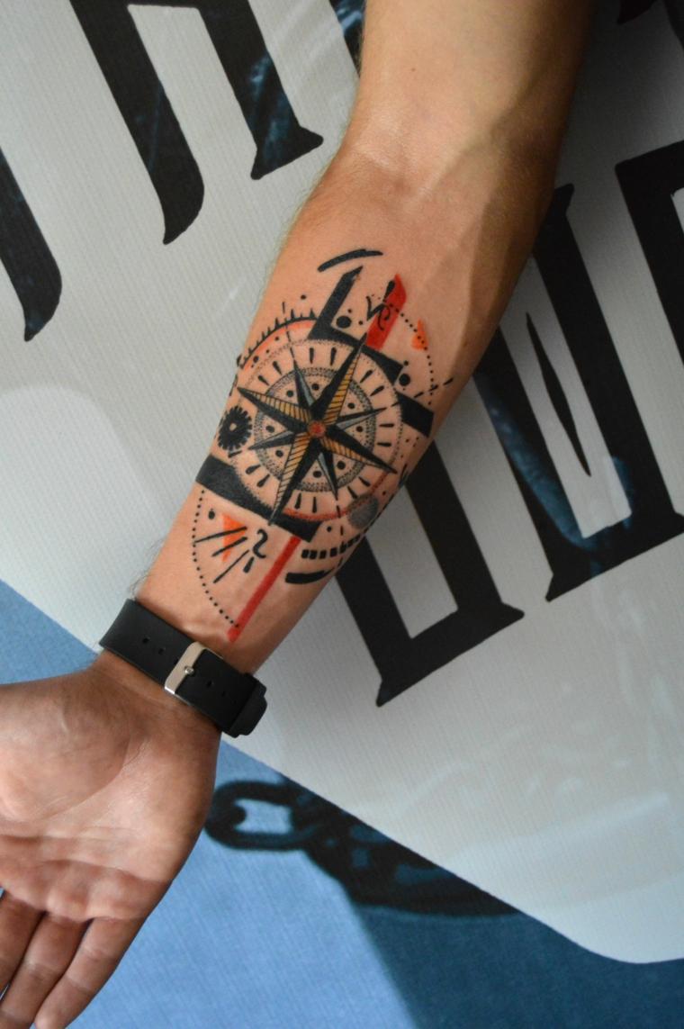 tattoo con disegno bussola in cerchio colorato tatuaggio sull avambraccio di un uomo