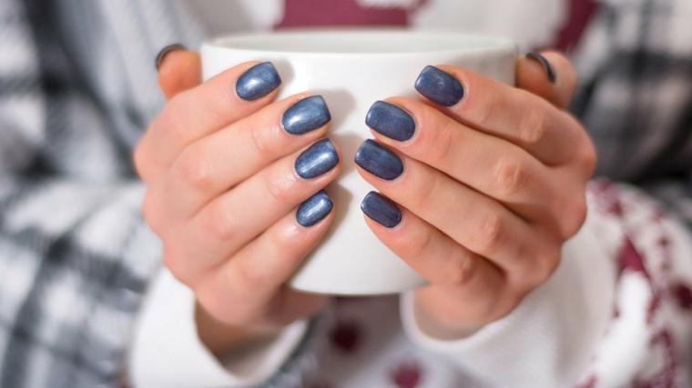 tazza nelle mani di una donna unghie con smalto colore blu manicure forma quadrata