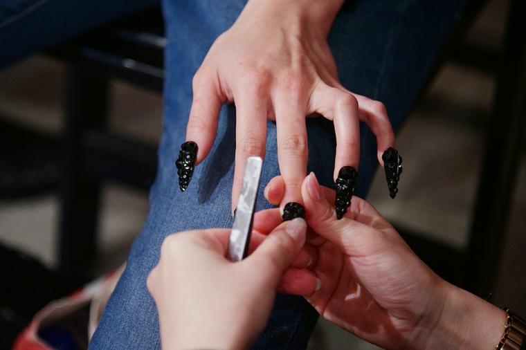 unghie gel autunno 2020 immagini smalto nero mat con brillantini sulla mano di una donna