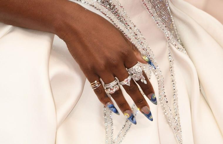 unghie stiletto colore smalto nude e disegno fiori donna con abito da sposa