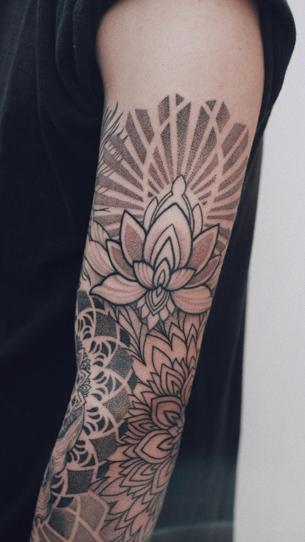 uomo con braccio tatuato tatuaggi con motivi mandala e disegno di fiore di loto