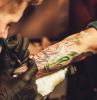 uomo con guanti che fa un tattoo idee tatuaggi uomo braccio colorati