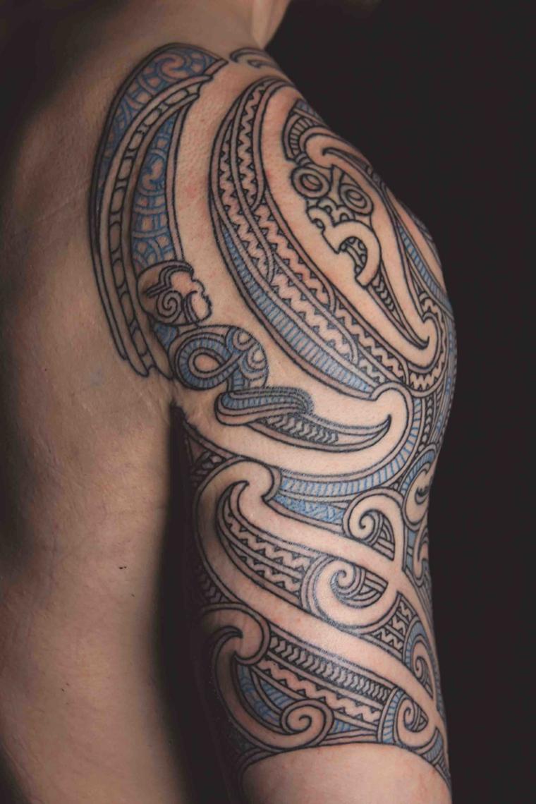 uomo con tattoo sulla spalla tatuaggio maori braccio disegno con ornamenti colorati di blu